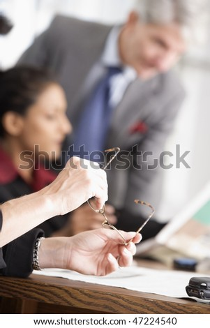 Holding eye glasses in a business meeting.