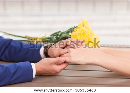 Holding fast. Man holding hands of his lovely girlfriend on background of flowers.