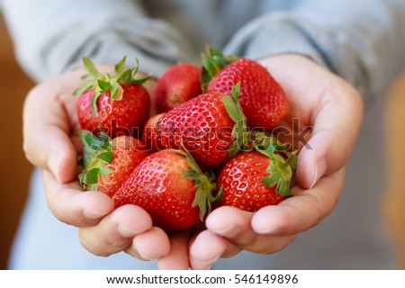 holding fresh strawberry in hands #546149896