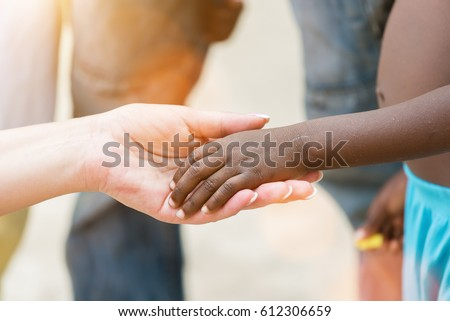 Holding hands.Caucasian woman's hand holding African black little girl's hand.Unrecognizable people, close up #612306659