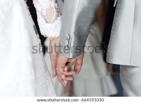Holding hands newlyweds in wedding theme #664591030