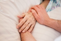 Holding hands of a patient in hospital and deathbed