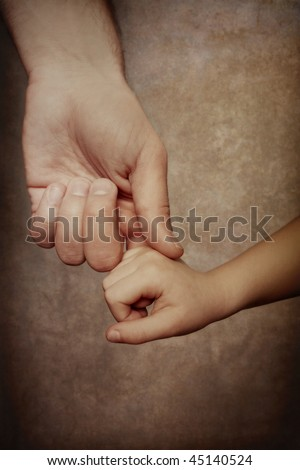 Holding Hands of Love. A father reaches down and holds the hand of his child