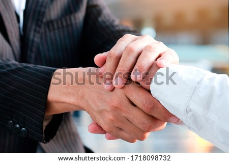 Holding hands with business partners to trust business partners, relationships to achieve future commercial and investment goals.