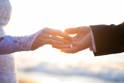 Holding Hands with wedding rings on the background of sea and sun.
