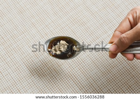 Holding in hand Ayurvedic herbal medicine syrup in spoon for cough, fever, seasonal flu etc Kerala India. Tulsi, dry ginger, jaggery, honey, camphor medicines from Ayurveda cure allergies, bronchitis.
