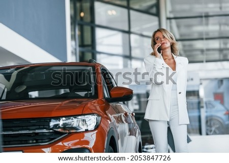 Holding phone. Woman in formal clothes is indoors in the autosalon.