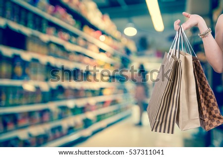Holding shopping bags by hand on Supermarket with Abstract blurred photo of store with trolley in department store bokeh background, Business shopping concept #537311041
