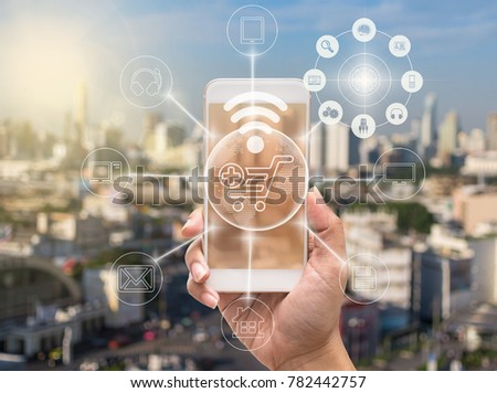 holding smart phone showing the mobile payments and online shopping with moni channel over the cityscape background,business omni channel or multi Channel concept