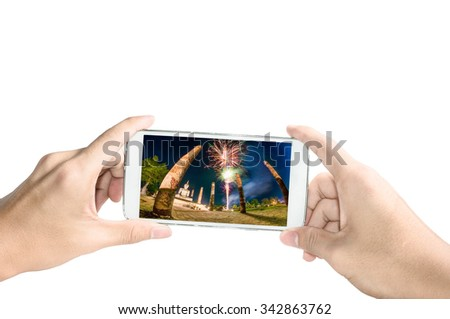 Holding smart phone take a photo of old temple in Sukhothai with firework on white background