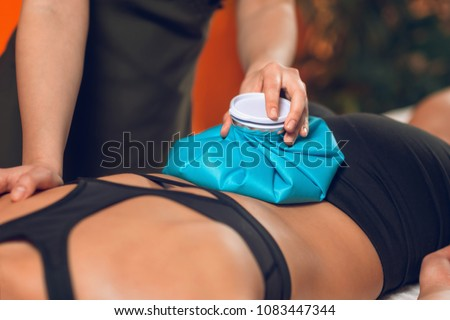 Holding the blue ice pack on the painful lower back. Stock photo ©