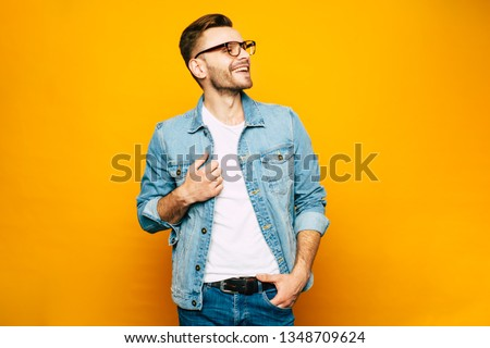 Holding the moment. Fair-faced man in the denim outfit which consist of a jacket and jeans mixed with bright white t-shirt and fashionable glasses in front of yellowish wall.