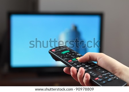 Holding TV remote control with a television as background - stock photo