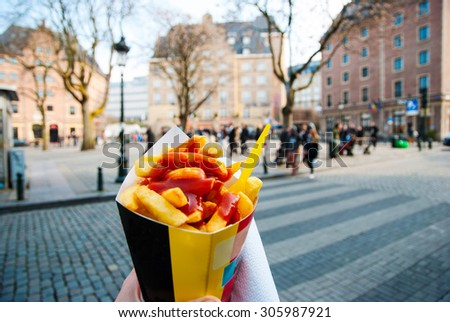 Holding typical belgian fries in hand in the streets of Brussels