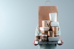 Holding various take-out food containers, pizza box, coffee cups in holder and paper bag, close-up. Light grey background, place to insert your text. Delivery man.