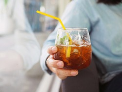 Holds a glass of ice black tea with ginger ale decorated with lemon sliced and mint. Lifestyle concept.
