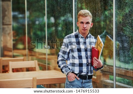 Holds notepads in hands. Portrait of young student that stands in cafe at rainy day. One person.