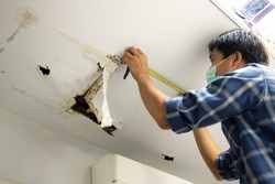 Hole damaged in ceiling house from pipes water leakage with worker repair and fixing ceiling panels. Office building or house problem from plumber system repairman service concept.