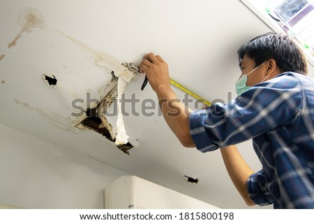 Hole damaged in ceiling house from pipes water leakage with worker repair and fixing ceiling panels. Office building or house problem from plumber system repairman service concept. Foto stock ©