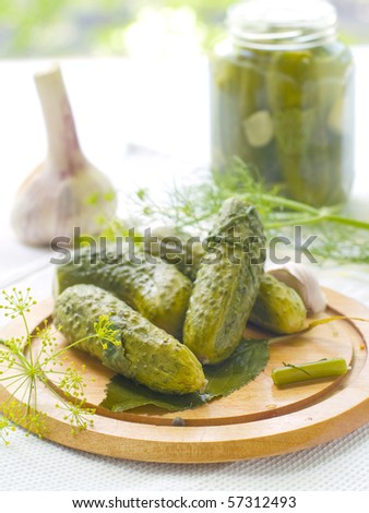 Hole fresh salted cucumber on plate with dills