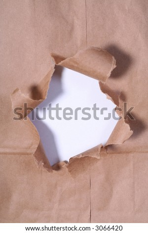 Hole in a brown paper bag backed with white paper