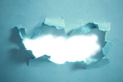 Hole in blue paper, abstract background