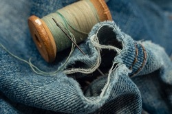 Hole in jeans. Needle with thread for darning jeans. Tools for work dressmaker, seamstress fashion designer