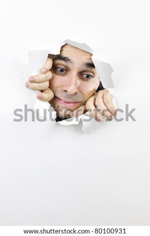 Hole in paper with frightened man looking down through
