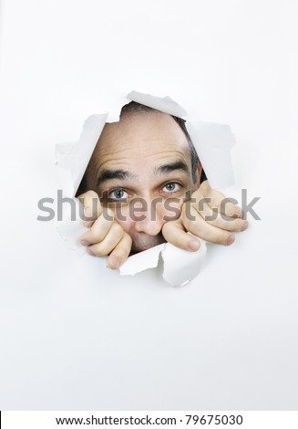 Hole in paper with scared man looking through