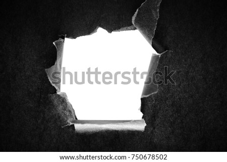 Hole in the black paper with torn sides
