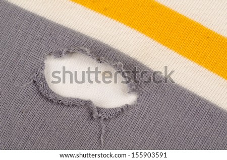 Hole in  the cotton fabric of a shirt