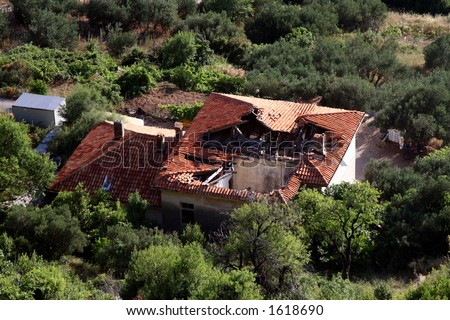 Hole in the house roof after earthquake - stock photo