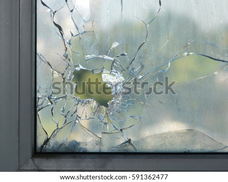 Hole in the window glass by a bullet shot during war shooting. Cracks spreading around the hole. Green leaves of trees blurred by the glass. Dirty window frame. View of a street from the inside.