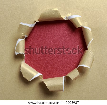 Hole ripped in gold paper on red background