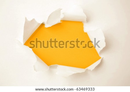 Hole ripped in white paper on orange background. Torn open. Copy space