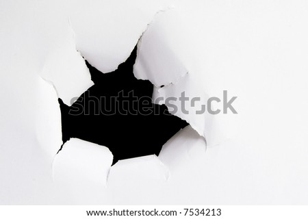 Hole ripped outward in a piece of paper - stock photo