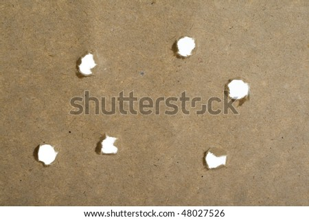 holes from the bullets of paper with hole