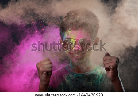 Holi festival colours blowing over the blurred face of a boy.Concept for Indian festival Holi