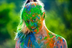 Holi powder on face. Beautiful young woman posing with exploding pink and green Holi powder around her body