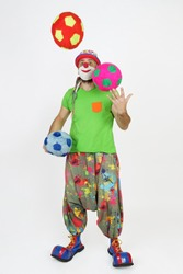 Holiday and fun concept. The clown juggles balls. Isolated on white