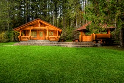 Holiday apartment - wooden cottage in forest in early spring with green grass on back yard and forest in background