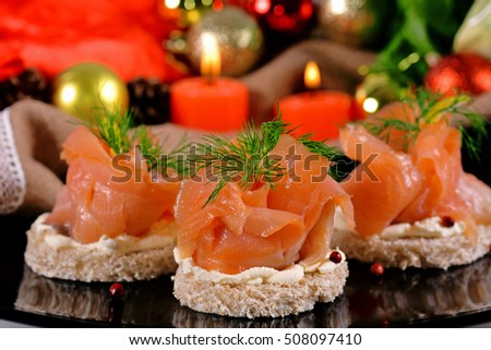 Holiday appetizer with salmon canapes on a background of Christmas decorations