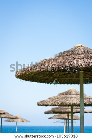 Holiday at sea concept: straw umbrellas against blue sky
