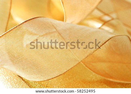 Holiday background image of metallic gold ribbon  curls on shiny  wrapping paper.   Macro with shallow dof. - stock photo