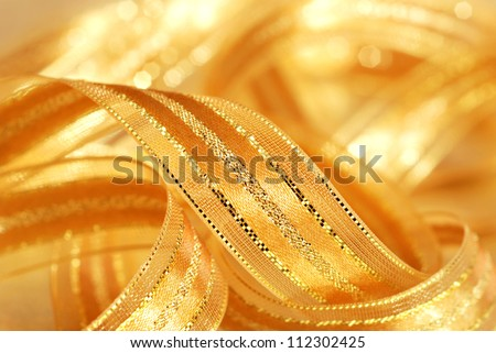 Holiday background image of shiny gold satin ribbon with copy space.  Macro with extremely shallow dof.