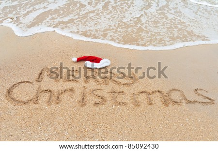Holiday background - Merry Christmas written on tropical beach sand