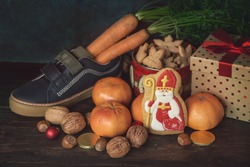 Holiday background Saint Nicholas, Sinterklaas, with children shoe with carrots, cookies, nut, tangerines, gifts and sweets