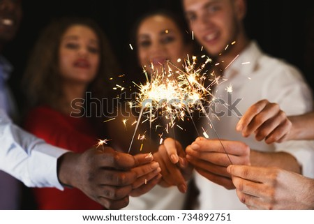Holiday background with sparklers. Young friends holding bengal lights, closeup, selective focus. Birthday or winter holidays celebration, greeting card mockup #734892751