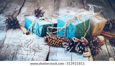Holiday Blue Boxes with Linen Cord, Cinnamon, Pine cones, Nuts. Natural Gifts on Wooden Background. Toned