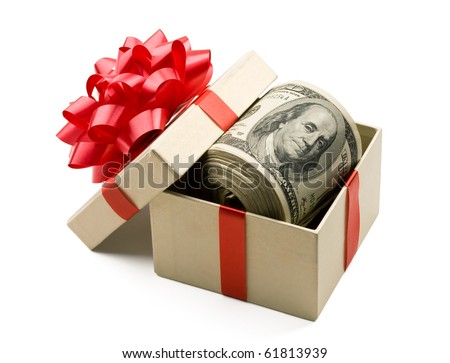 Holiday bonus.  Money roll laying in red bow decorated gift box.